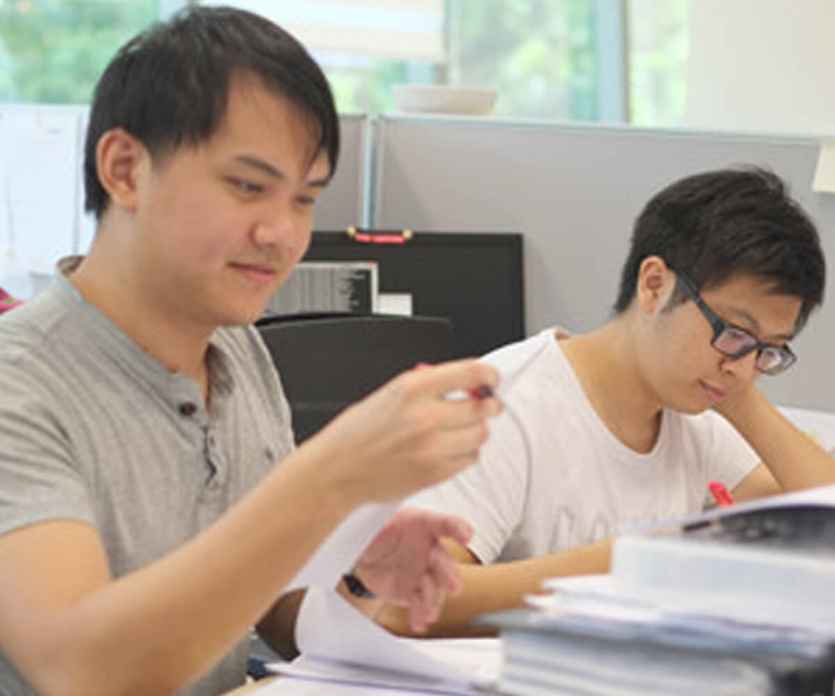 Graduates Michael Tay and Julian Teh sit at a desk reading papers