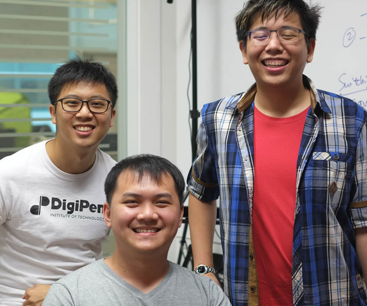 Graduates Michael Tay, Julian Teh, and Koh Naimin pose for a photo in an office