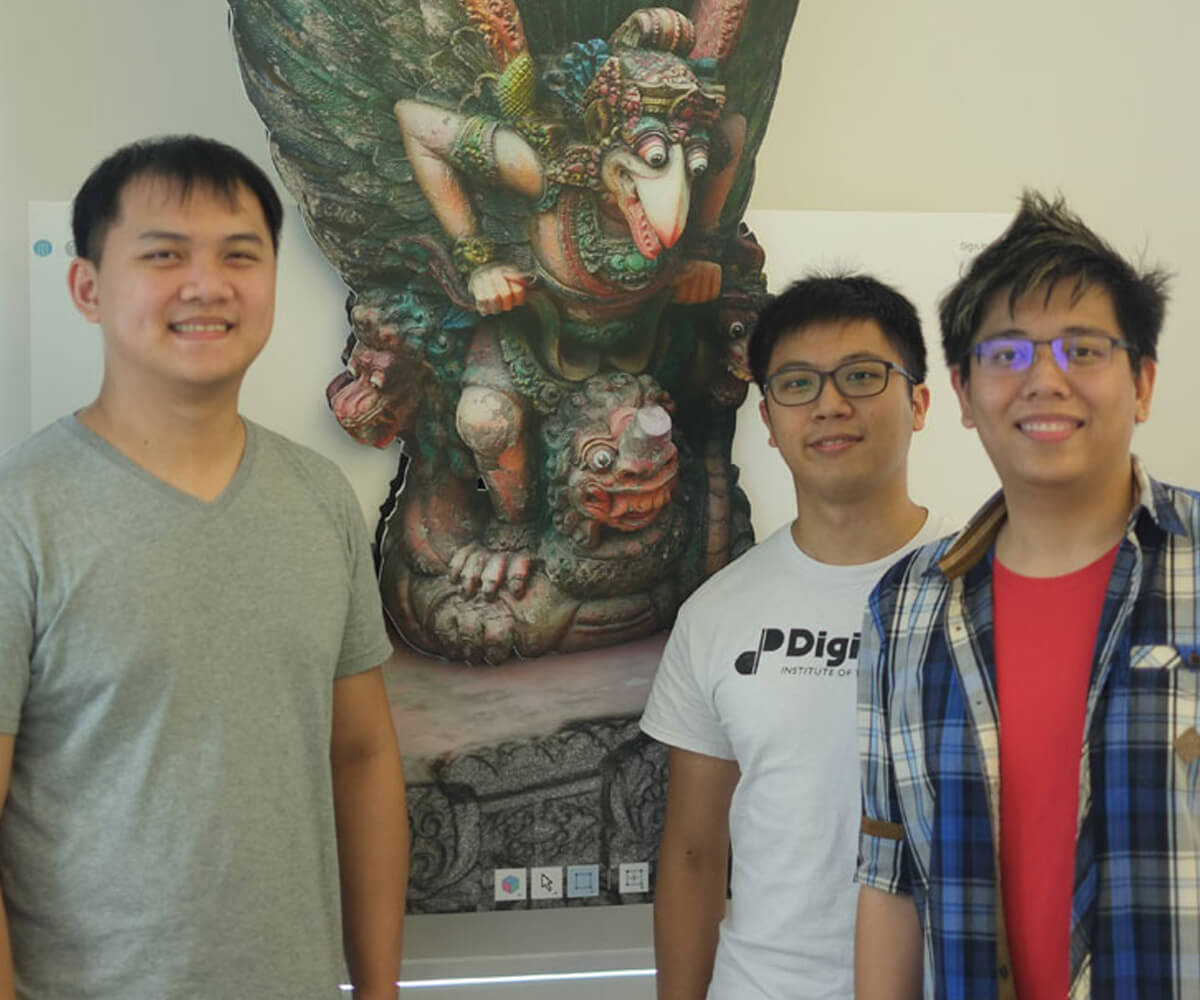Graduates Michael Tay, Julian Teh, and Koh Naimin pose in front of an ornate cutout in the style of Southeast Asian sculpture