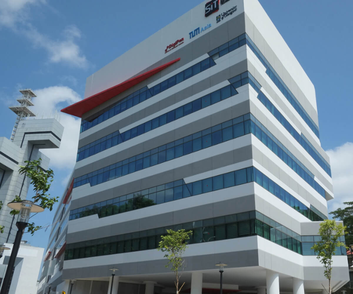 Modern, six-story building with red, white, and gray accents. Several company logos adorn the top right corner.