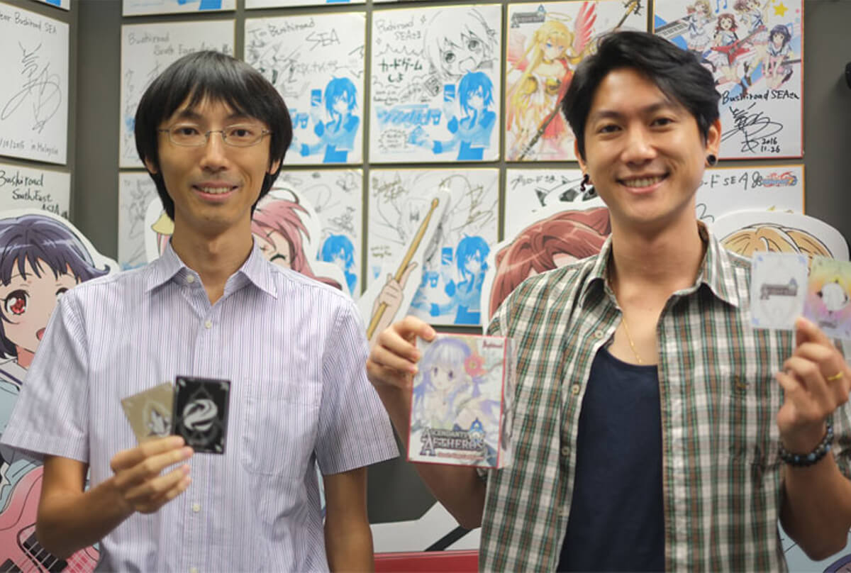 Graduate Rudy Ng and Shunichi Taira pose for a photo while holding cards from the Ascendants of Aetheros game