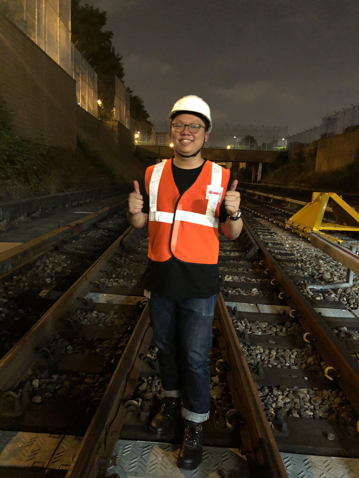 Samuel Tan dons a worker's vest and gives two thumbs up while standing on train tracks at night.