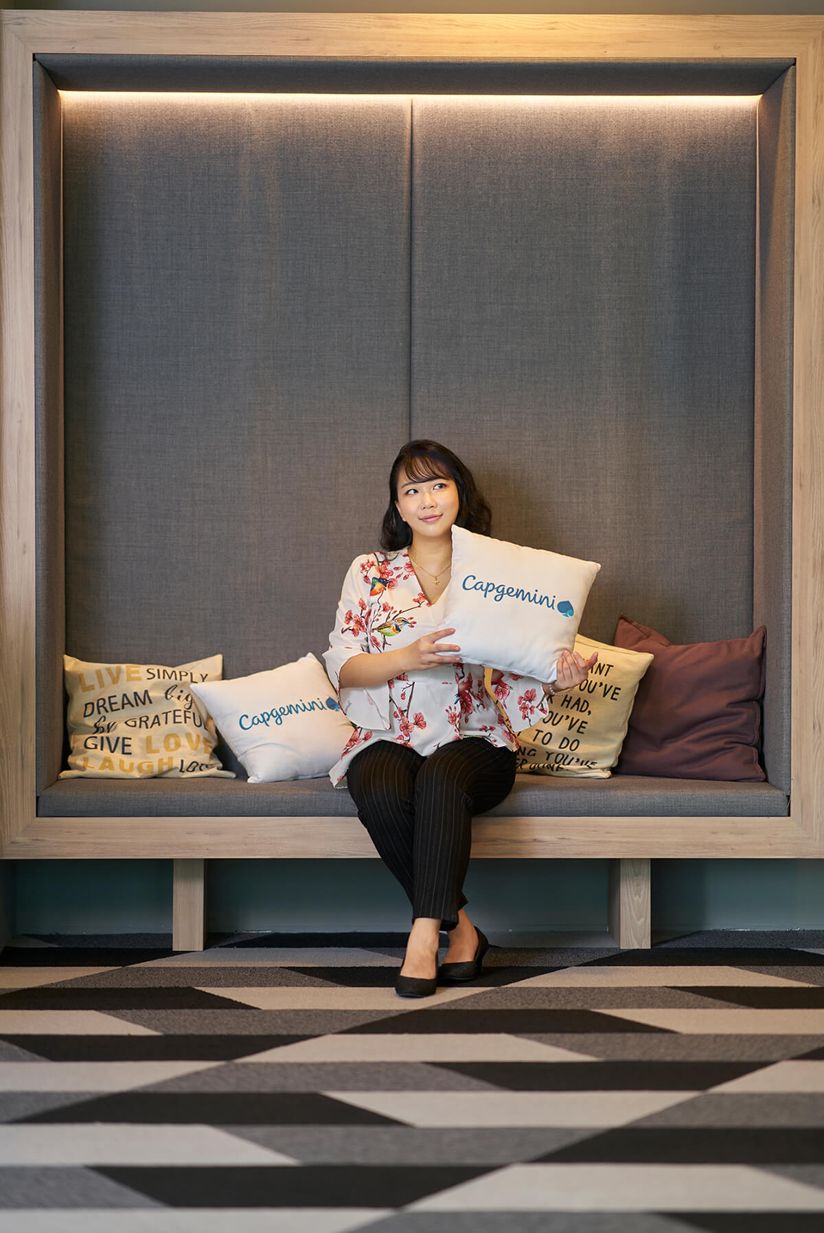 DigiPen (Singapore) grad Sherilyn Kan poses with a Capgemini pillow