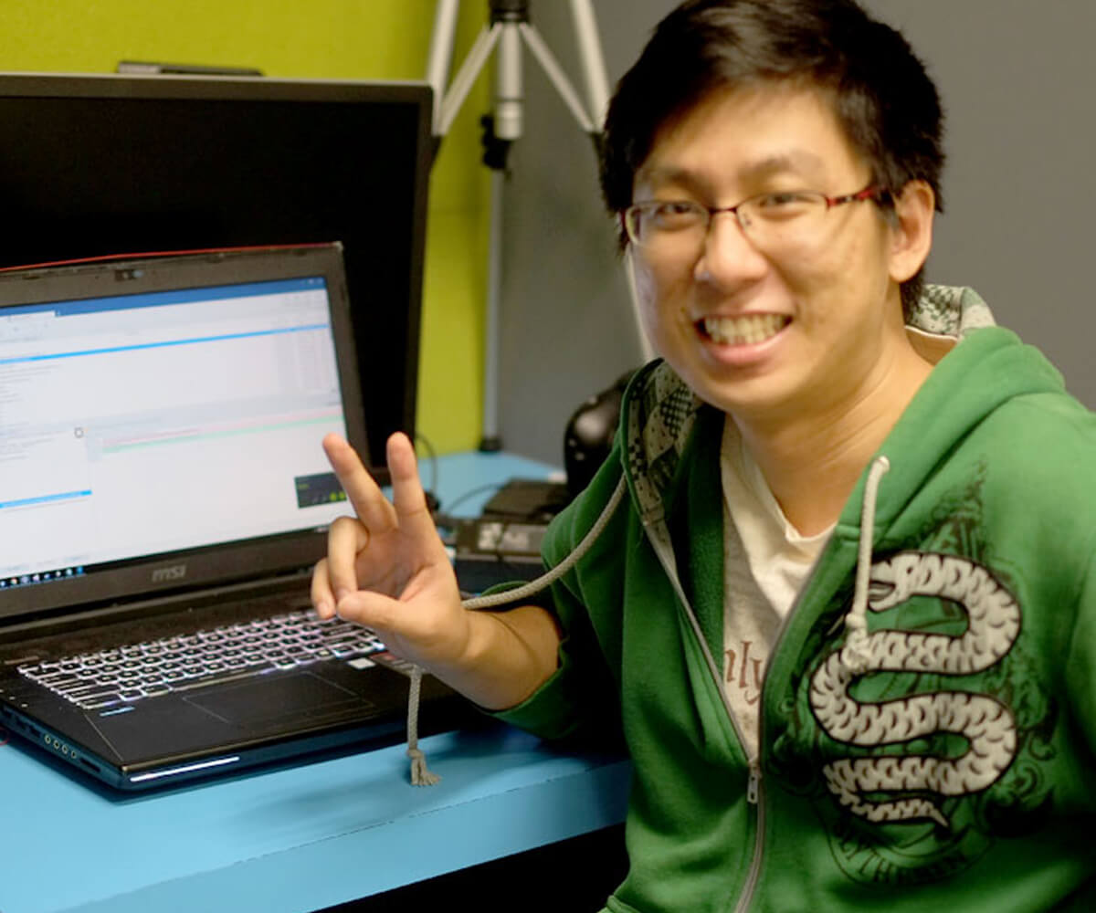 DigiPen graduate Sim Wei Jin seated at a desk with a laptop posing for a photo while giving a V sign with his hand