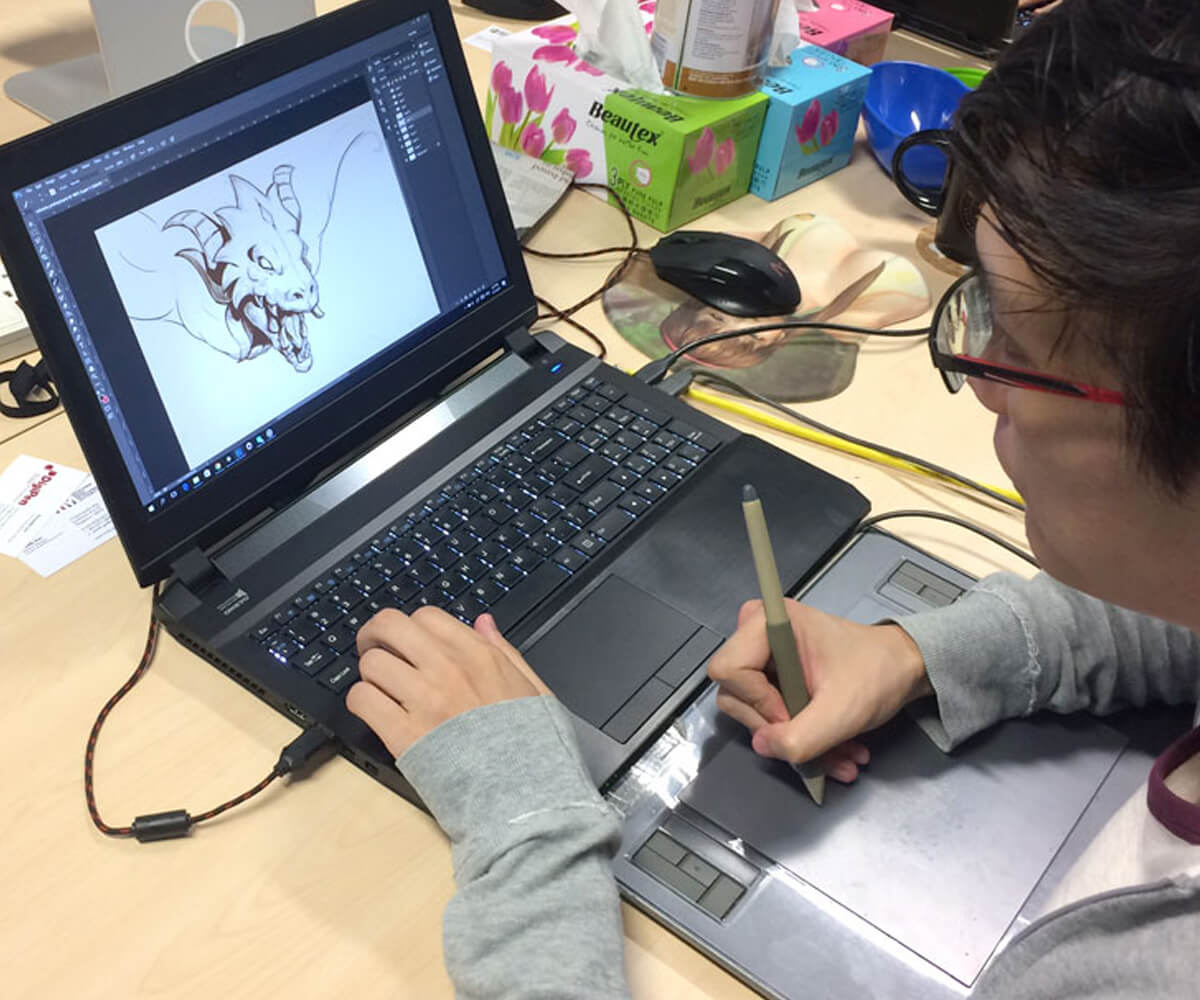 Alumnus Desmond Wong works on a dragon illustration using a laptop computer and tablet